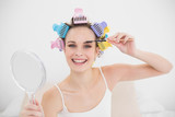 Happy natural brown haired woman in hair curlers brushing her ey
