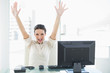 Euphoric stylish brunette businesswoman raising her arms