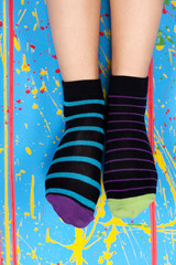 female legs in striped socks over colorful ink splashes wall