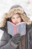 Attractive young adult man in winter clothes reading a book
