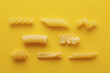 Different types of pasta on yellow background