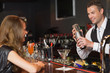 Handsome bartender serving cocktail to beautiful woman