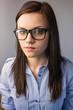 Serious pretty brunette wearing glasses posing