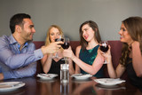 Friends clinking red wine glasses at a bar