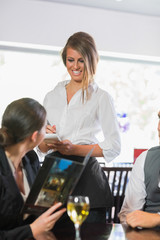 Businesswoman ordering dinner from pretty waitress