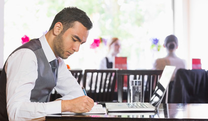Concentrated businessman writing something