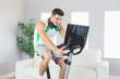 Stern handsome man training on exercise bike using laptop
