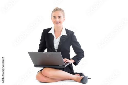 Cheerful blonde businesswoman sitting on floor working with her