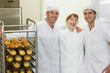 Three young bakers posing together in a bakery