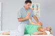 Handsome physiotherapist manipulating patients arm