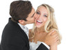 Handsome bridegroom kissing his wife on her cheek