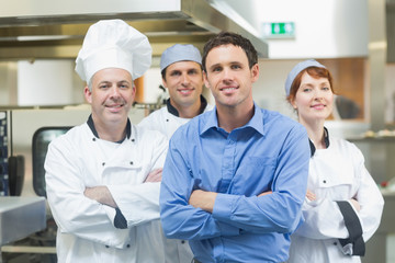 Young manager posing with some chefs