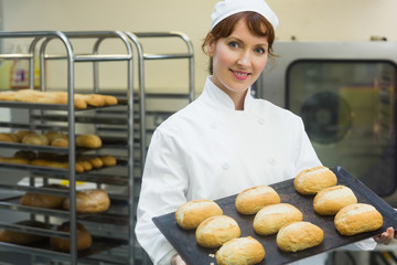 Happy female baker showing some rolls on a baking tray