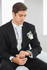 Young bridegroom watching the clock