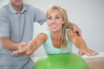 Physiotherapist correcting patient doing exercise on exercise ba