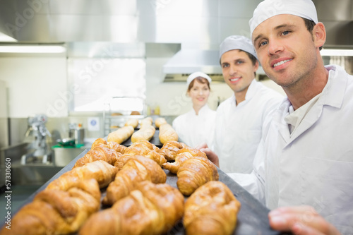 Three young bakers posing in a bakery