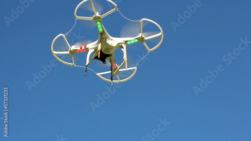 Quadrocopter flying overhead against a blue sky