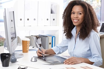 Smiling office worker with drawing table