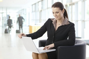 Businesswoman working on laptop at lobby