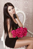 Amazing sexy brunette girl holding bouquet of pink roses. Valent
