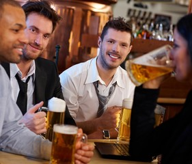 Group of friends drinking beer at pub