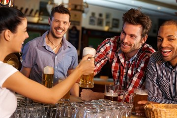Friends drinking beer at counter in pub