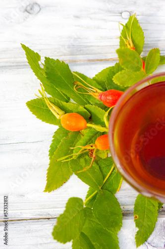 Чашка целебного чая с ягодами шиповника на деревянном фоне