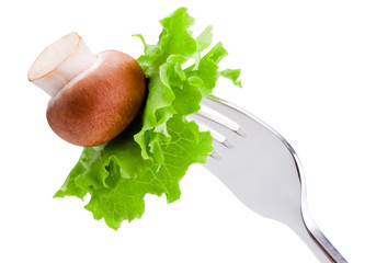 Mushroom and Leaves of green salad on a Fork Isolated on white b