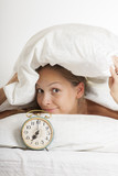 Young woman with alarmclock on the bed at morning