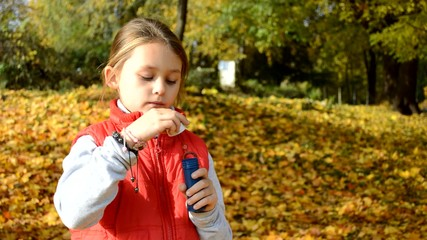 Girl blows soap bubbles on a background of yellow foliage