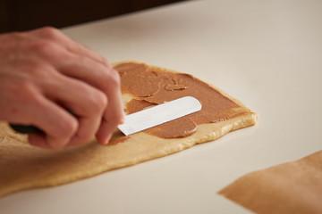 Baker putting cinnamon cream on brioche dough