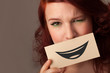 Happy pretty woman holding card with funny smiley