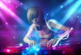 Fototapety Energetic Dj girl mixing music with powerful light effects