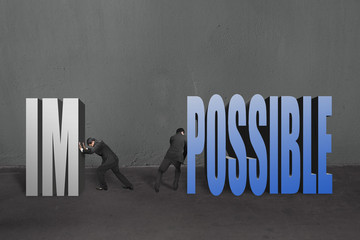 "Two businessmen separate word ""impossible"" to IM and POSSIBLE, t"