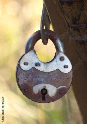 Old rusty padlock on brown wood door hangs outdoors close up