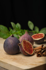 Fig, cutted fig and cinnamon sticks on wooden cutting board.