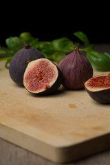 Fig, cutted fig and basil on wooden cutting board.
