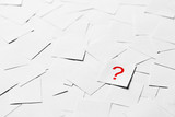 Note paper with question mark on a pile of blank papers