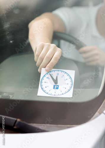 man placing parking clock on car dashboard