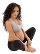 Very cute, small, pregnant woman sits in her workout clothing.