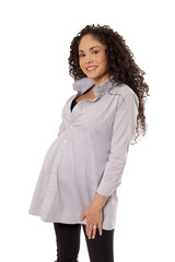 A pregnant woman flashes a big smile in her maternity shirt.