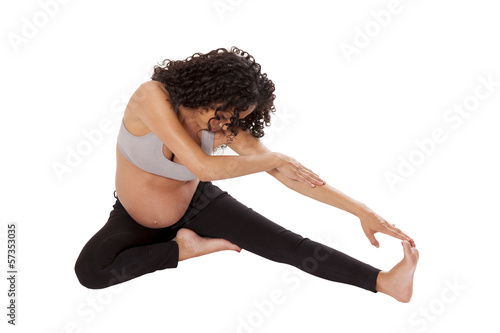 A very pregnant woman stretches before exercise.