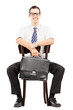 Young businessman holding a briefcase and waiting on a chair
