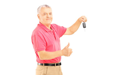 Smiling senior man holding a car key and giving thumb up