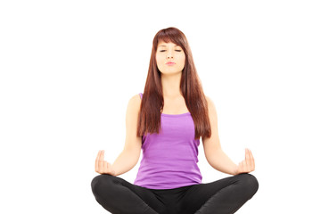 Young female athlete in outfit sitting on a floor and meditating