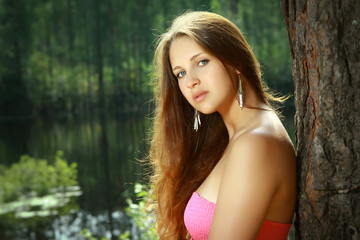 Girl, 16 years old, in pink dress, by the lake.