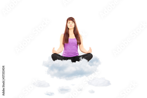 Young female athlete in outfit sitting on clouds and meditating