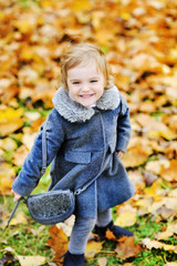 Cute little girl playing in autumn park