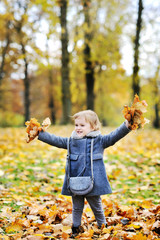 Little girl tossing leaves in autumn park