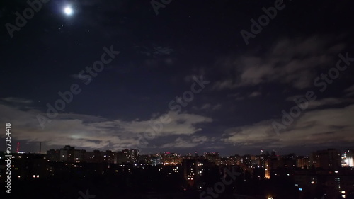 Night city timelapse, houses buildings shine lights, clouds move